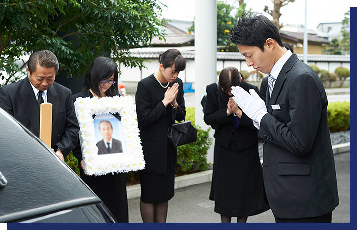 遺族に手を合わせる男性葬祭ディレクター